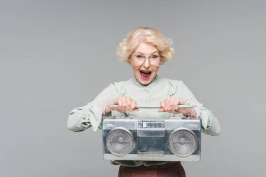 Shouting senior woman with boombox isolated on grey stock vector