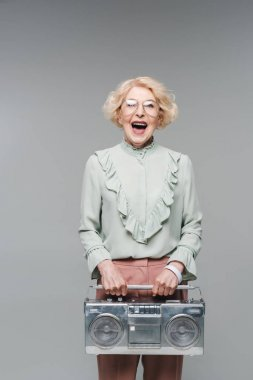 Shouting senior woman with vintage boombox isolated on grey stock vector