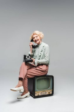 beautiful senior woman talking by rotary phone while sitting on vintage tv on grey
