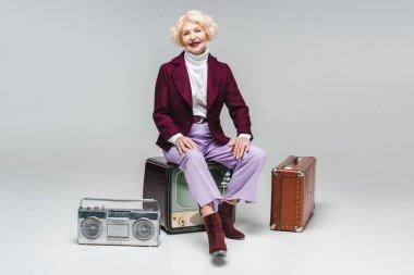 Attractive senior woman sitting on vintage tv on grey stock vector