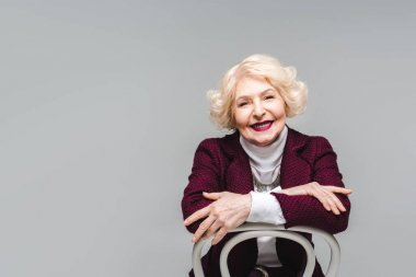 smiling senior woman sitting on chair and looking at camera isolated on grey