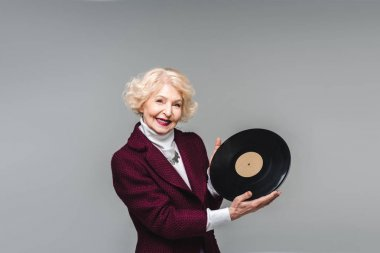 happy senior woman holding vinyl disc isolated on grey