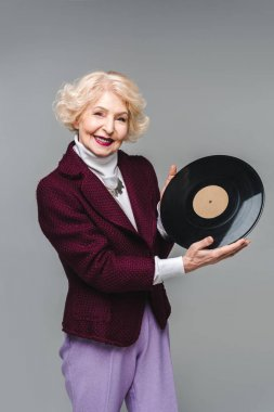 beautiful senior woman holding vinyl disc isolated on grey