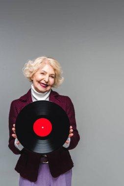 smiling stylish senior woman holding vinyl disc isolated on gray background