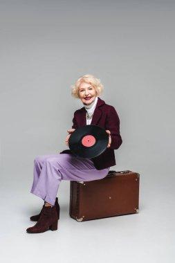 happy stylish senior woman with vinyl disc sitting on vintage suitcase on gray background