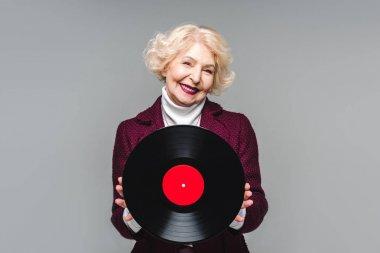stylish senior woman holding vinyl disc isolated on gray background