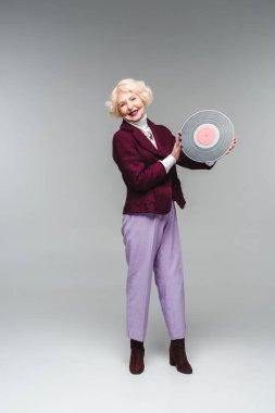 happy stylish senior woman holding vinyl disc on gray background