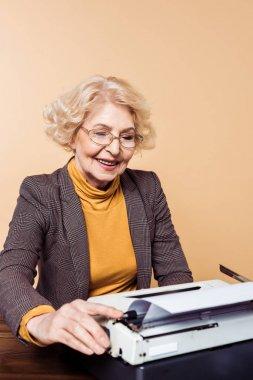 smiling stylish senior woman in eyeglasses using typewriter