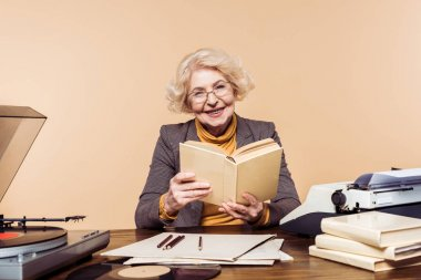 smiling senior woman in eyeglasses with book sitting at table with vinyl disc, record player and typewriter
