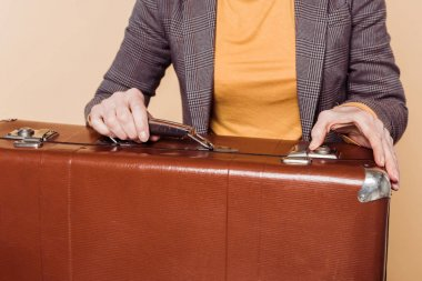 cropped shot of stylish woman closing vintage suitcase isolated on beige background