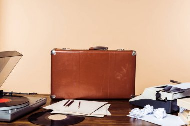 vintage suitcase, vinyl disc, record player and typewriter on table