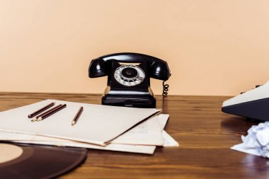 closeup shot of rotary phone on wooden table with typewriter and vinyl disc on table