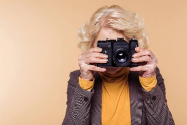 senior woman shooting on film camera isolated on beige background