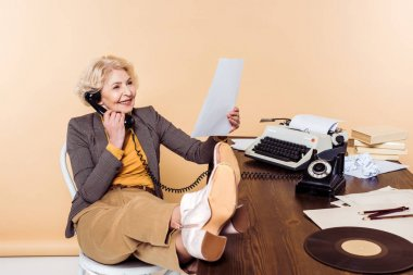 smiling senior woman with legs on table talking on rotary phone and looking at pape