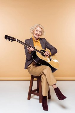 smiling stylish senior woman sitting on chair and playing on acoustic guitar