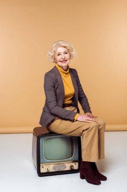 Smiling stylish senior woman sitting on vintage tv stock vector