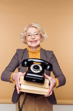 stylish senior woman in eyeglasses holding rotary phone and stack of books
