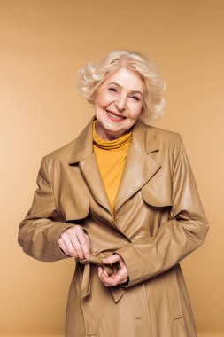 smiling fashionable senior woman tying belt of leather trench coat isolated on beige background