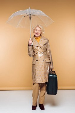 fashionable senior female traveler in trench coat with umbrella and suitcase