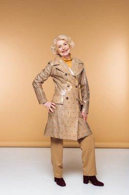 happy stylish senior woman posing in trench coat