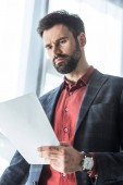 Photo bottom view of handsome young businessman reading business document