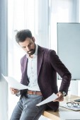 handsome young businessman doing paperwork while leaning back on desk at office