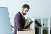 fired young businessman putting books and folders into box