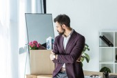 dismissed young businessman looking at box of personal stuff in office