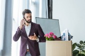Fotografie fired young businessman talking by phone near box of personal stuff at office