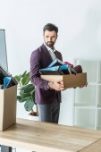 Photo fired young businessman carrying box of personal stuff at office
