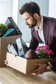 fired young businessman taking box of personal stuff from desk at office