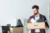 Fotografia licenziato il giovane uomo daffari con le scatole di cose personali in ufficio
