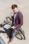 Fényképek csinos fiatal üzletember újságok hajlik vissza a kerékpár és kávé, hogy menjen magas szög kilátás