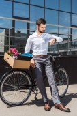 young manager with box of personal stuff on bicycle looking at wristwatch