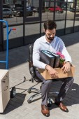 Fotografie young sad dismissed manager with box of personal stuff sitting on chair outdoors