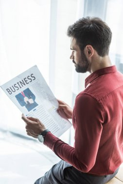 handsome young businessman reading newspaper at office