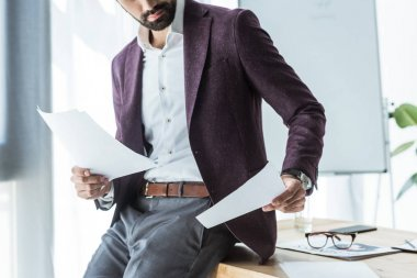 cropped shot of handsome young businessman doing paperwork