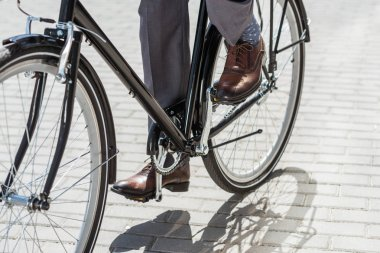 Cropped shot of businessman in classic shoes riding vintage bicycle stock vector
