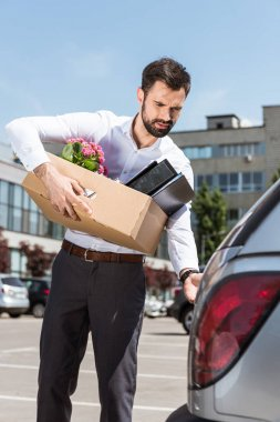 young manager with box of personal stuff opening car trunk on parking