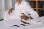 oříznutý obraz africká americká podnikatelka sedí u stolu a držení tužky v sadě office