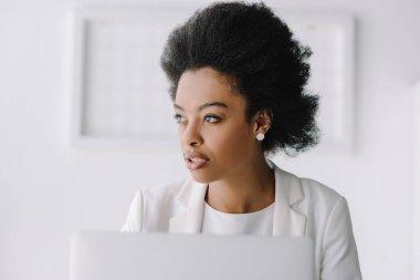 portrait of attractive african american businesswoman looking away in office
