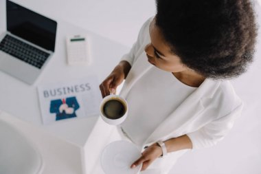 high angle view of attractive african american businesswoman holding cup of coffee near table in office