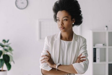 attractive african american businesswoman standing with crossed arms in office