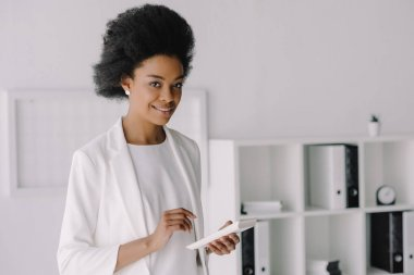 attractive african american businesswoman holding calculator in office