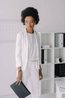 attractive african american businesswoman standing with small bag in office