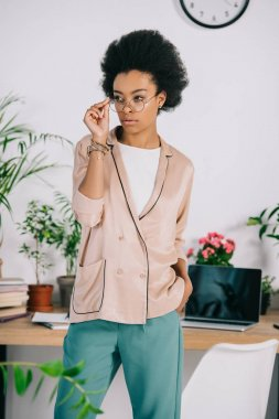 attractive african american businesswoman standing near table in office and touching glasses
