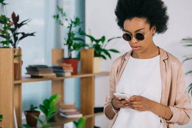 Attractive african american businesswoman in sunglasses using smartphone in office stock vector