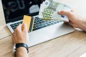 Fényképek vágott lövés a személyi hitelkártya és az euro-bankjegyek felett laptop