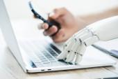Detailní pohled člověka a robota rukou pomocí smartphone a notebook na dřevěný stůl
