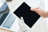 Detailní pohled lidské ruky a robotické paže držící digitální tablet s prázdnou obrazovkou